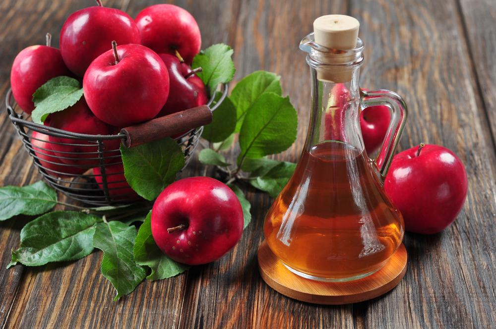 Un tazón de manzanas al lado de un frasco de Vinagre de Manzana
