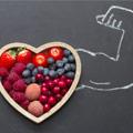Cuenco de fruta en forma de corazón, con un brazo musculoso dibujado con tiza a la derecha