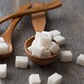 Terrones de azúcar en una cuchara de madera.