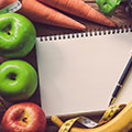 Comida variada, con una libreta y un boli en el centro de la imagen