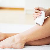 Mujer depilándose las piernas con máquina eléctrica