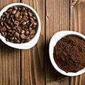 Dos cuencos de café: uno con café molido y otro con granos de café.
