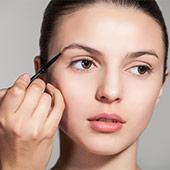 Mujer a la que maquillan las cejas