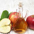 Botella de Vinagre junto a manzanas rojas.