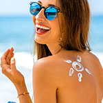 Mujer protegiendo su piel del sol con un protectora solar