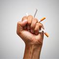 Puño aplastando cigarros