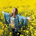 Mujer con los brazos abiertos en un campo de flores