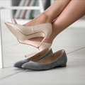 Mujer trabajadora cambiando zapatos de tacon por zapatos planos