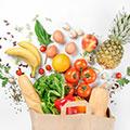 Bolsa de la compra con comida colorida que sale de la bolsa