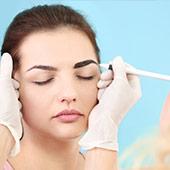 Mujer que aplica un tinte de color en las cejas de una mujer joven