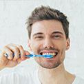 Hombre lavándose los dientes con un kit de blanqueamiento dental