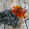Vaso de Té negro sobre Té negro en virutas.