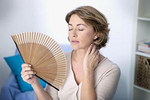 Mujer sufriendo sofocos por la menopausia