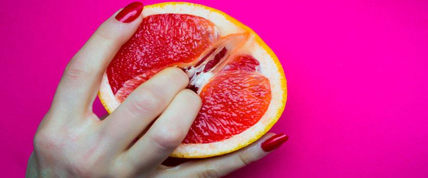 Dedos de mujer apretando una naranja roja