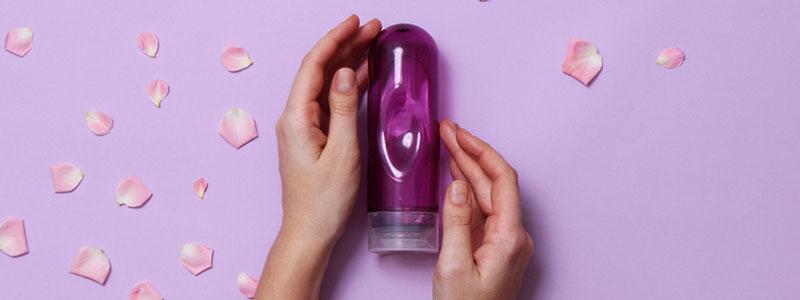 Lubricante Intimo en un fondo rosa con pétalos.