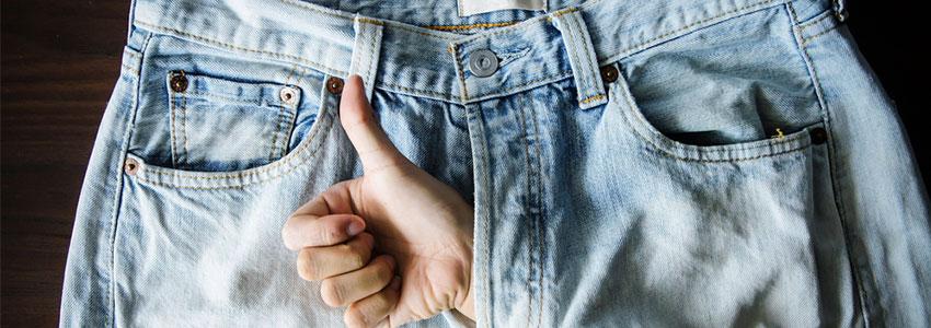 Jeans de hombre con una mano con el simbolo de OK por la bragueta