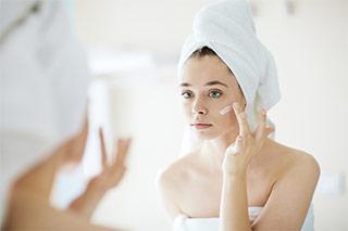 mujer aplicando crema para hiperpigmentacion
