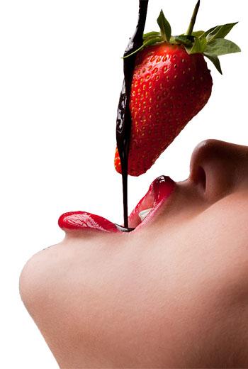 Mujer sensual comiendo fresa con chocolate