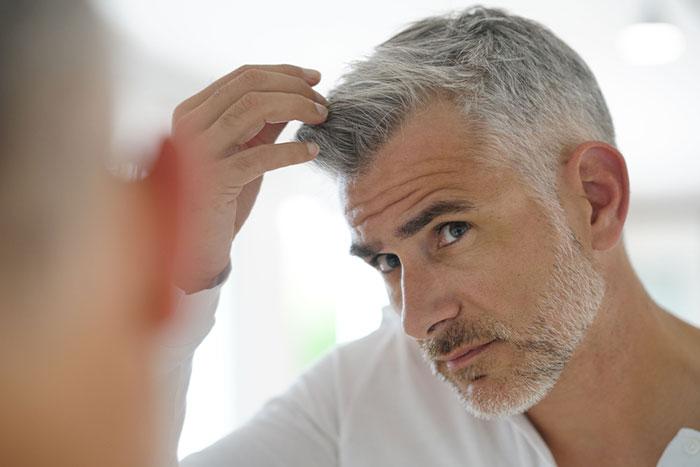 Hombre de mediana edad, con el pelo blanco y mirándose al espejo.
