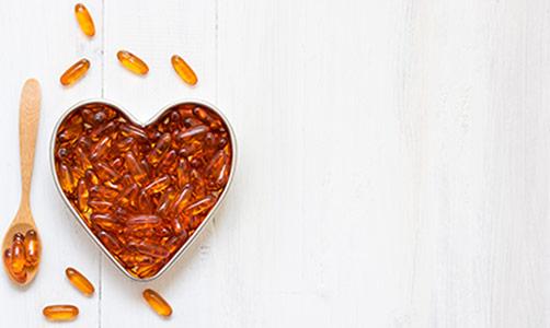 Plato de cápsulas de Omega 3 en forma de corazón.