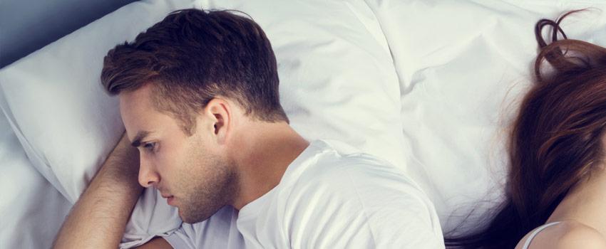 Hombre preocupado recostado en la cama junto a mujer