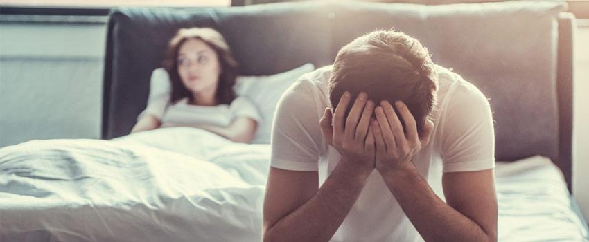 Hombre triste al borde de la cama, con una mujer enfadada a su espalda.