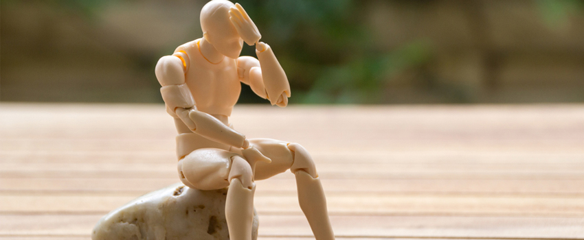 Muñeco articulado representando un hombre sentado con la cabeza baja.