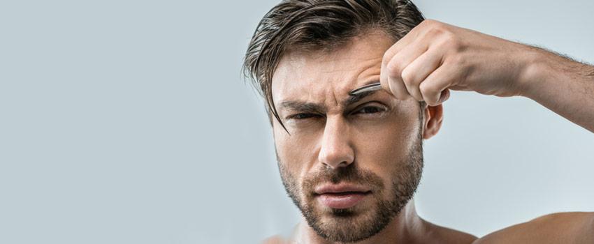 Hombre depilandose las cejas