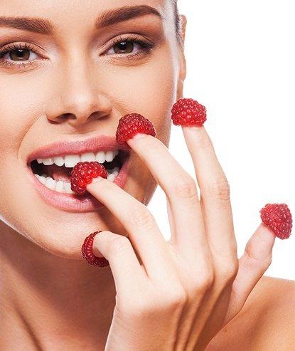 Mujer comiendo frambuesas con los dedos